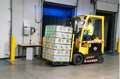 A man operating a forklift and lifting a few boxes.