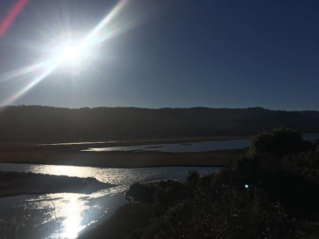 sunshine over still water with hills behind
