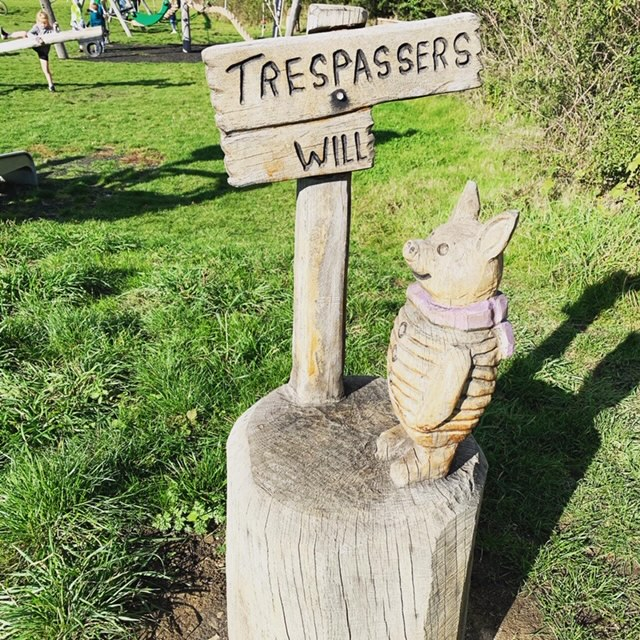 Wooden Piglet figurine with 'trespassers will' sign