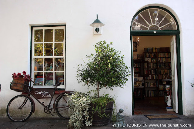 Bicycle with flower basket leaned on the white facade next to the open entrance door of a bookshop
