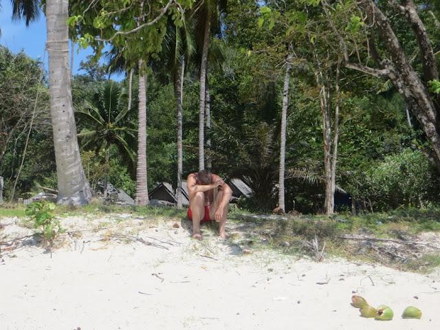 Парень сидит на пляже