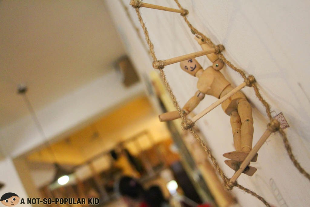Wooden Doll climbing a ladder in Cafe Noriter