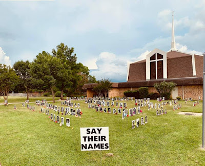 The Say Their Names Memorial displayed on the lawn at a church; black and white headshots with names of Black people killed unjustly, with flowers at each picture