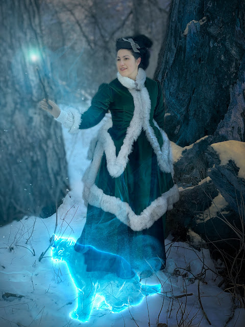 the author in 1870s winter dress, holding a stick that has been photoshopped into a glowing wand surrounded by translucent smoke effects