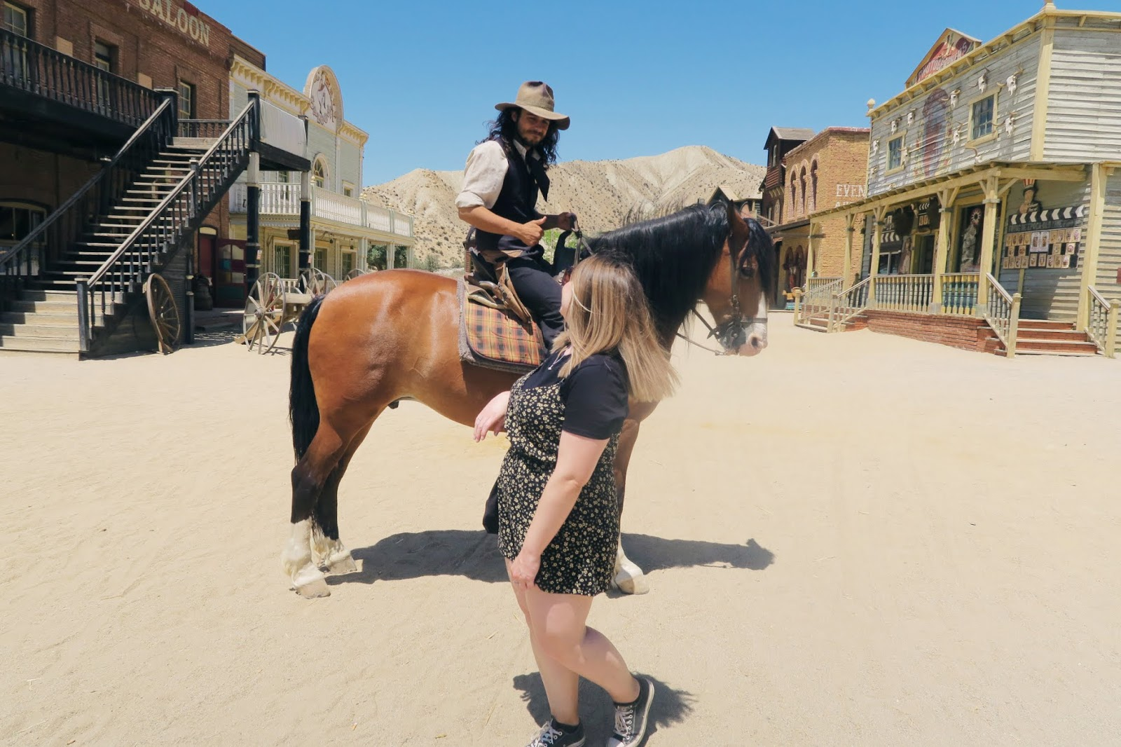 Standing in front of a cowboy on a horse at Mini Hollywood
