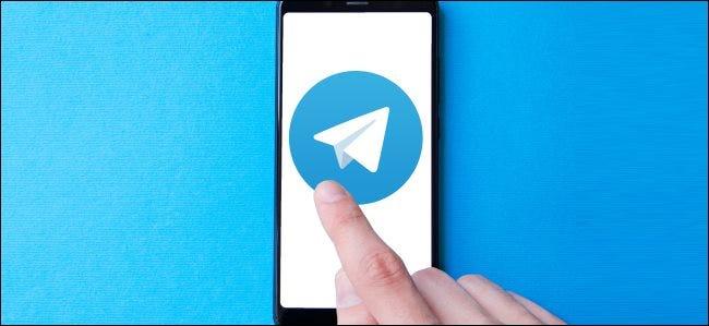 النقر بإصبع على أيقونة تطبيق Telegram الكبيرة على الهاتف الذكي.