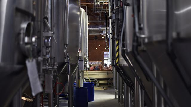 diners at the end of a row of brewing tanks