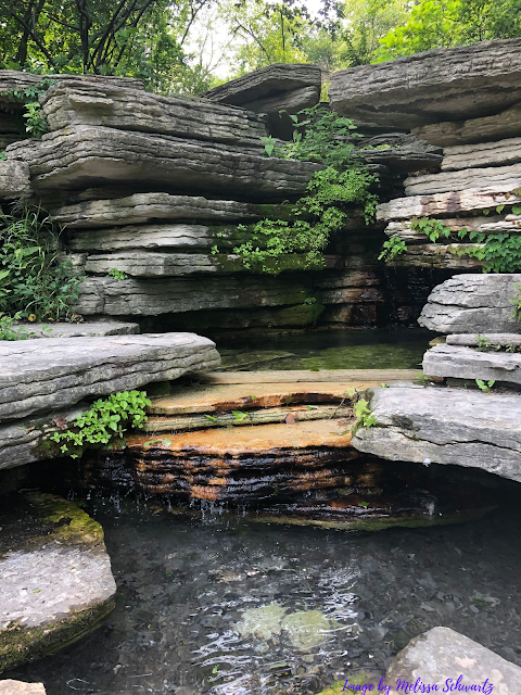 A waterfall gently tumbles over layered rock ensconced with green leaves  at Alfred Caldwell Lily Pool in Lincoln Park, Chicago.
