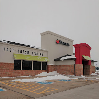 """the front of a Fazoli's restaurant is visible, with the words """"Fast. Fresh. Italian."""" visible on a creamy wall with green awnings and a large tomato next to the restaurant name"""