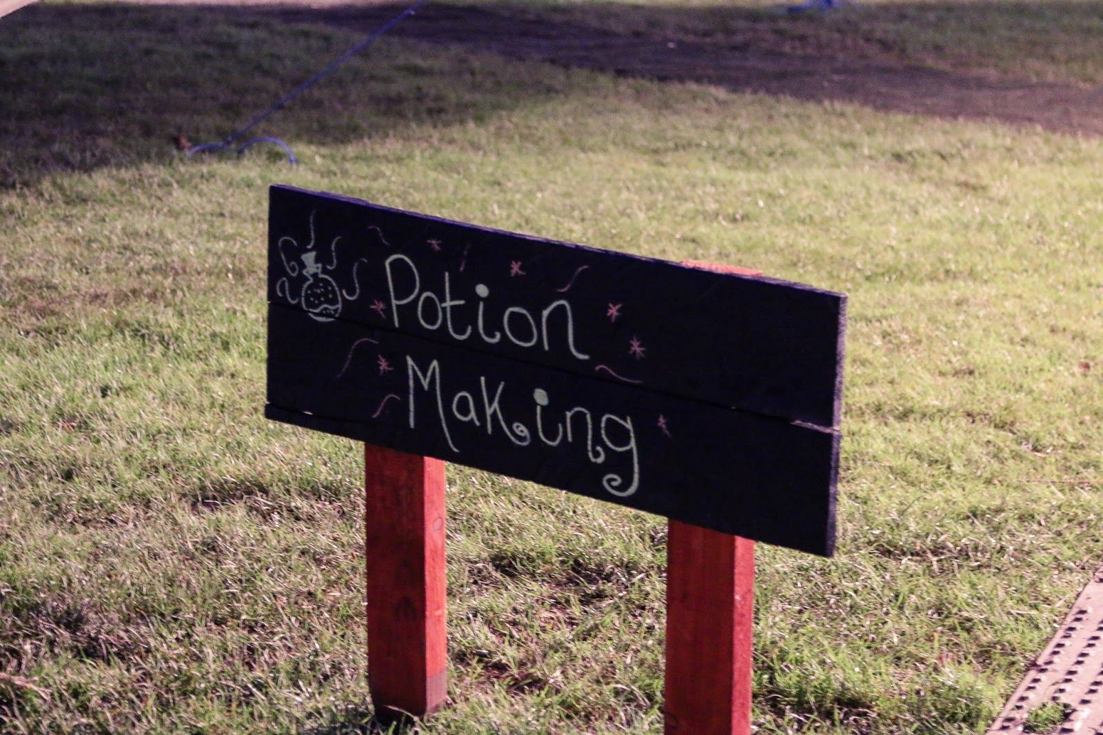 "Close up photo of the sign for the Potion making station - a slate sign with ""Potion making"" written in white"