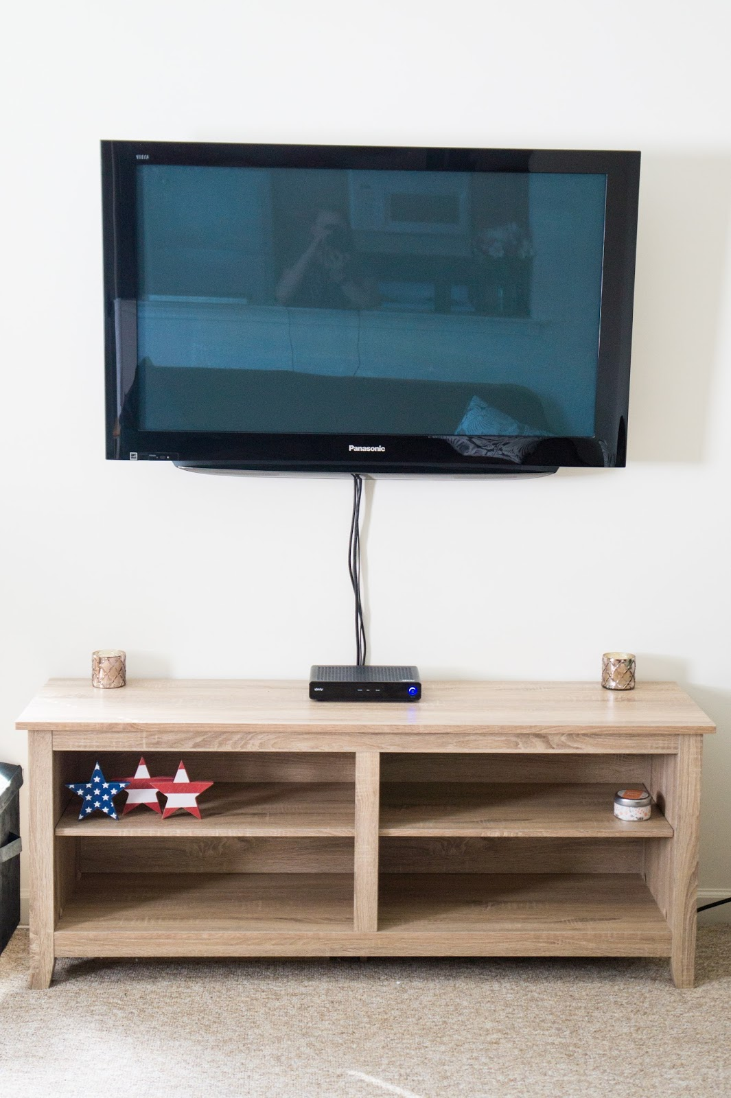 TV mounted on a wall over a natural wood TV stand.