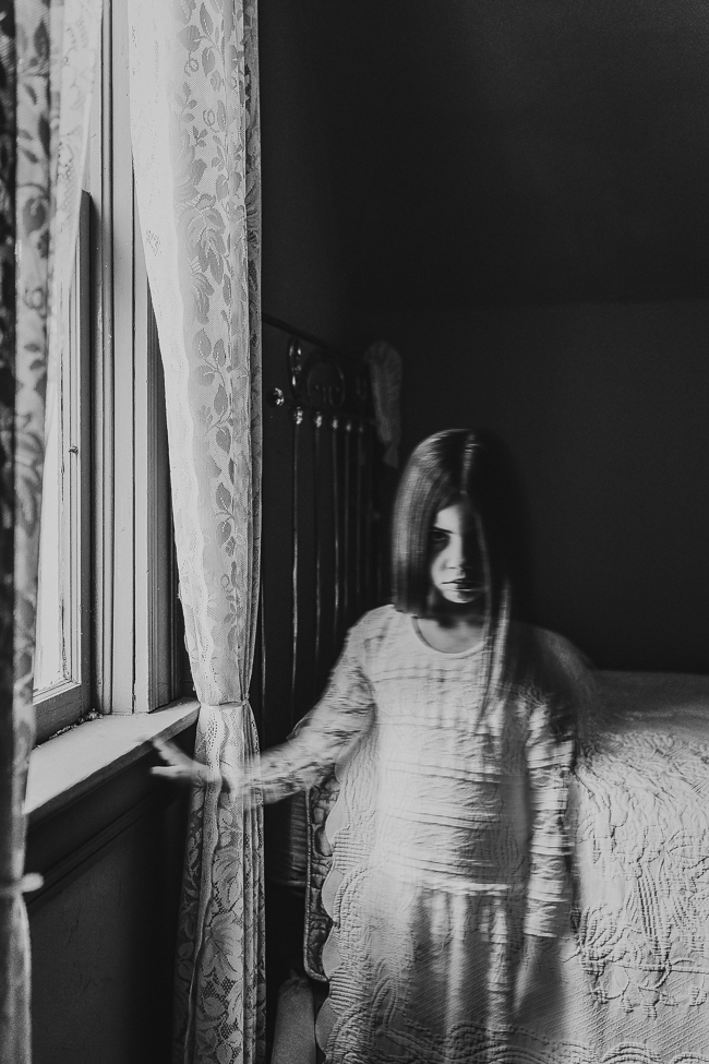 little girl ghost standing next to a window in an old home
