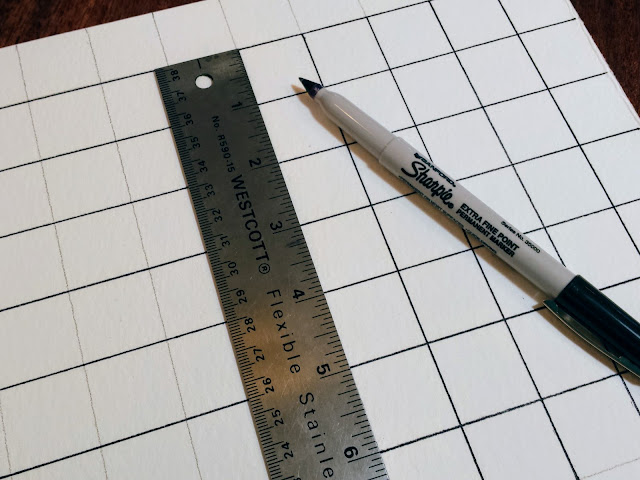 Drawing the grid on watercolor paper with permanent marker and ruler.
