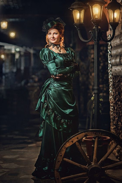 Woman wearing green satin steampunk victorian dress with matching hat, black lace gloves, and choker necklace with cameo.