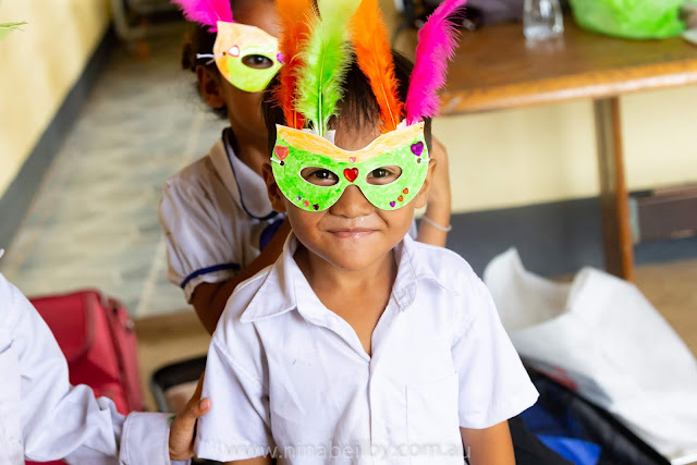 Very small Cambodian boy posing with his craft creation, a mask with feathers and diamantes.