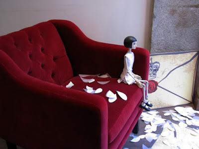 Marioneta sentada num cadeirão vermelho