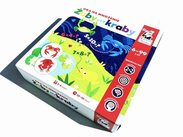 na zdjęciu pudełko gry żaby czy kraby gra na mnożenie, na pudełku widzimy kawałek łąki z żabami i kawałek oceanu z krabami, są też informacje że gra jest dla osób w wieku 6-99, dla dwóch do czterech graczy i trwa 20 do 40 minut