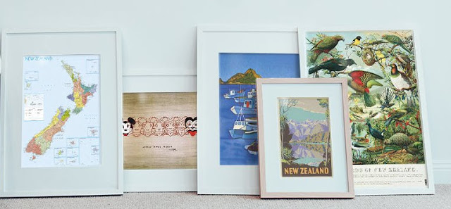 A row of framed New Zealand art prints leaning against a wall