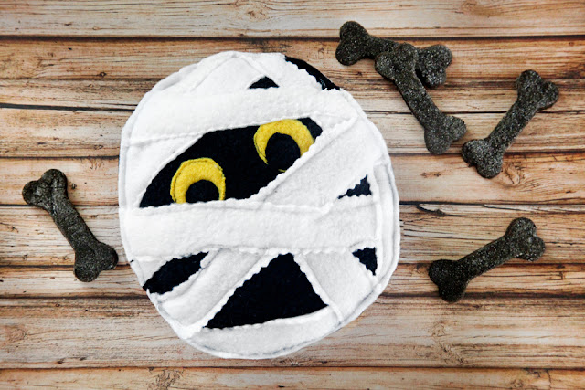 Homemade Halloween mummy face dog toy on a table with black bone dog treats