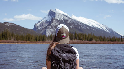 Alone girl with backpack enjoying the mountain landscape