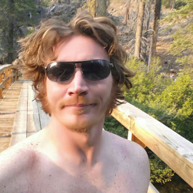 Crazy haired half naked hiker on a bridge