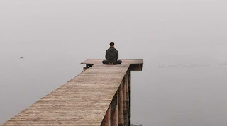 Man practicing mental relaxation by still waters