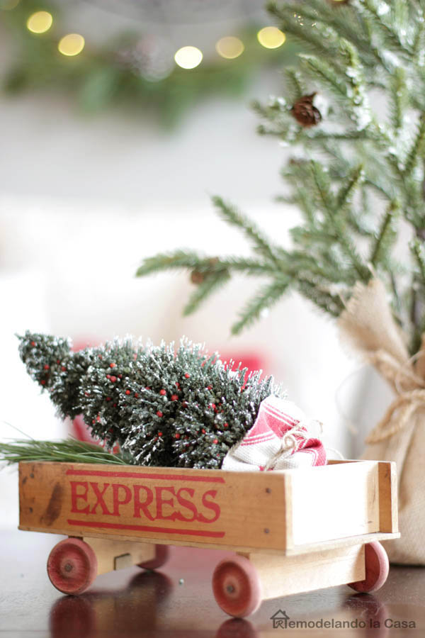 Express wooden wagon on coffee table as a little dosis of vintage decor, brush tree
