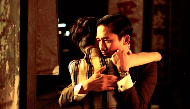 "Film Review:  Wong-Kar-Wai is a Hong Kong second wave filmmaker. He wrote screenplay, produced and directed together 'In The Mood For Love' in 2000.Though the introduction of the film starts with some of the common scenes, he creates some extra-ordinary scenes and makes the film extra-ordinary with his skills.  Introduction,naming and accessory discussion:-  Hong Kong Filmmaker Wong-Kar-Wai directed some other films before. As a result of getting successful of those films, he starts to direct his 'In The Mood For Love'. At first, he gave a Chinese name of the film ''the age of blossoms'' or ''the flowery years'' which is derived from a song of a same name by Zhou Xuan from a 1946 film. The English Title of the film derived from the song ""In The Mood For Love''. At first, Wong-Kar-Wai kept it secrets but after listening the song from the film he selected the title and gave the name ''In The Mood For Love''. It was one of the great films of 2000s. Besides, it is one of the important and noticeable films in Asia. It is also the second part of his 'Trilogy'. The first part or film is 'Days of Being Wild' (1990) and the last part is ''2046'' released in 2004.  Plot of the film:   Hong Kong-1962:  The event of the film takes place in 1962. There are two main characters. Chow-Mo-Wan and Su Li-zhen. Mr. Chow is married and a reporter of a Newspaper. His office is in Hong Kong. On the other hand, Su Li-zhen is also married. She works at a shipping company as a secretary. Both Mr. Chow and Su Li-zhen simultaneously come to rent their different flats. But they rent their flats alongside. Sometimes, Su comes down from flat to buy food. As both of them stay at the second floor, sometimes when they come down and go on at the stair, they meet and say 'Hi', 'Hello'. Both of them simultaneously come to home from their jobs and they meet for a very short time. Su's husband Mr. Chan is in Japan for business. On the other hand Mr. Chow's wife is also in abroad for business. Both of them are busy with their deeds. So, they can't come to home such that. Meanwhile, there is made a relationship between Mr. Chow and Mrs. Chan (Su). They start their conversation at a hotel about tie and vanity bag. Chow says, 'Your bag is very beautiful and extra ordinary. Where have you bought it? A bag is needed for my wife too.' Su says, 'Her husband has taken it from abroad.' But she adds that Mrs. Chow also uses this kind of a bag. Mr. Chow says 'Yes'. He says her boss has given it to her. On the other hand, Su says, 'your tie is very beautiful and attractive. From where have you bought it? Mr. Chow says, 'My wife has taken this buying from abroad. This kind of tie is unavailable without abroad.' But Su knows her husband sometimes wears this kind of tie by borrowing. She tells about this to Mr. Chow. Thus a relationship is made up between them. After few days, they can know that their husband and wife have a different relation, besides business, and Mrs. Chow is also in Japan with Mr. Chan. Who knows how much deep their relationship is! But thinking about these matters, when Mr. Chow and Su fall in love, they are able to know this latter. Chow feels sick. Su cooks for him secretly. Even the owner of the flat of Chow, Mr. Koo also can't know. On the other hand, the owner of the flat of Mr. Chan, Mrs. Suen and her family can't know about their relationship and their deeds. The relationship of them becomes deeper. But they admit that their relationship is not like them (Mrs. Chow and Mr. Chan). They won't vitiate their pure love. Su regularly watches film. On the other hand, Chow writes 'Martial Arts' for the paper. But Su like to read this. Once, both of them write discussing it. There is no lack of money of Mr. Chow and Su. But they can only talk with each other sometimes at stair, sometimes at the street. But no other can talk at home. If the owners of those flats are able to know about their relationship, for this, they sometimes talk at stair, sometimes at the street, sometimes going to buy foods. Once, Mr. Chow rents a room at a hotel. Both of them congregate at the hotel room. They talk about their matters, they talk about their wife and husband. They try to have food which their wife and husband like to eat, though it was a very difficult task. During eating at the hotel, Su says, 'Tell, do you have a relation with a mistress or a woman?' Chow is in this scene. But they do rehearsal purposing Mr. Chan. Su lonely weeps not to able to keep secret her sorrows before Chow. Chow consoles her. Thereafter, they simultaneously, are coming back from office. It is raining. Chow takes an umbrella for Su. But Su says, 'you go home taking the umbrella. If I take this, they will suspect me.' Thus they express their love. But once, Chow tells Su, 'Could you purchase a ticket for Singapore?' He has got a job there. He will go there. Latter, Chow tells her to purchase another ticket for her so that she also can go with him. But before reaching of Su at the hotel, Mr. Chow goes to Singapore alone.  Singapore:-1963Su comes to Singapore after one year. Chow works at 'Singapore Daily'. Su phones there but without talking with Chow, she phones off. Mr. Chow can know that Su came there looking the cigarettes packet and lipstick. Chow meets his friend Ping at a hotel. 'Hi, Ping, if anyone's past life is hidden with such a big secret, is it shareable with anyone?' 'What do you say?' Ping does not say anything. There is no idea of him. Chow replies himself he should go to hill. After whispering these secrets into any whole the whole should be closed with mud. The secrets will prevail there forever. Ping says, 'What a sorrow! He tells Chow to express clearly.' But Chow won't talk to anybody. Chow gets a phone of Su. Then he goes Hong Kong.  Hong Kong:-1966Chow goes to Hong Kong after three years. After reaching there, he can know that the owner of his home, 'Koo family' has gone to Indonesia and also can know that the owner of Su's home, Suen family has gone to the U.S.A. Mr. Chow , showing Su's home to a person says, ' who stays there?' The person says, 'a woman and her cute baby.' After that Mr. Chow goes to Cambodia. But he doesn't know that Su and her baby are at the house.  Cambodia:-1966 Mr. Chow comes to Cambodia in the same year. He comes to a ruined monastery at Angkar Wat in Seim Reap, Cambodia. He whispers for sometimes into a hollow in a ruined wall, before plugging that with mud. He remembers all about his and Su's past moment of love and the events.  Incidental discussion and Conclusion: 'In the Mood for Love' (2000) is simultaneously written, produced and directed by Wong Kar-Wai. The film is starred by the famous actor and actress Maggie Cheung and Tony Leung. The acting of the main two characters is acted by them. The best work of the film is its background music composed by Michael Galasso and Shigaru Umebayashi. The cinematography of the film is executed by Christopher Doyle and Mark Lee Ping Bin. The film is edited by William Chang and distributed by Universal Pictures. In this film, Wong Kar-Wai, actually has given the importance of love and the narratives between a lonely married woman and a lonely married husband. Their wife and husband have an unethical relationship. But their (Chow & Su) relationship is not unethical, it is pure. They have come closer. But they have defeated to ethics. The director has pointed out and expressed this narrative to the audiences skillfully."