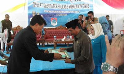 Perwakilan BKKBN Sulut tengah menyerahkan pesan Presiden RI, saat pencanangan kampung KB di Boltim