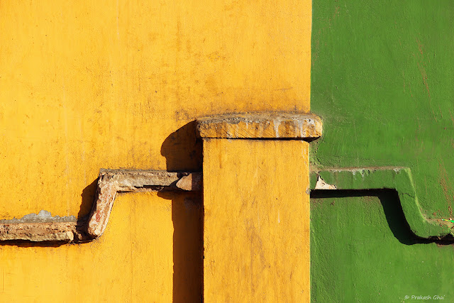 A Minimalist Photograph of a Wall with two primary colors, yellow and green.