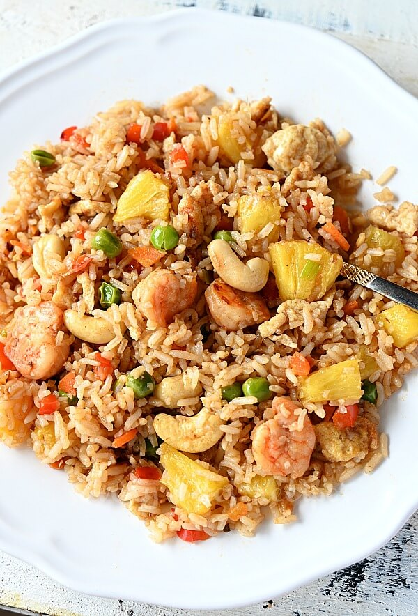 a white plate with pineapple fried rice