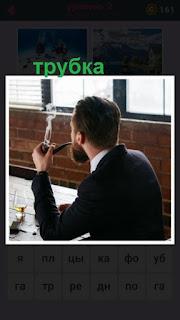 мужчина в костюме сидит за столом и курит трубку с бородой