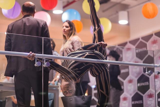 Atração contorcionista de Humor e Circo se apresentando durante o coquetel de evento de inauguração empresarial.