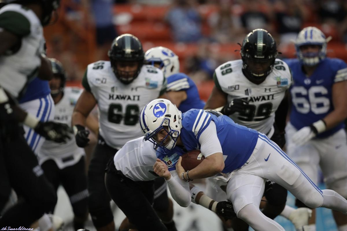 BYU quarterback Zach Wilson gets tackled during the 38-34 Cougar loss to Hawaii in the 2019 SoFi Hawaii Bowl in Honolulu on Tuesday, Dec. 24, 2019.