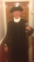 A gentleman in tricorn hat and 18th century coat holding a goblet of wine