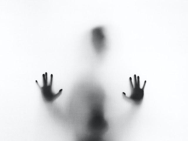 Silhueta de pessoa com mãos apoiadas atrás de vidro fosco