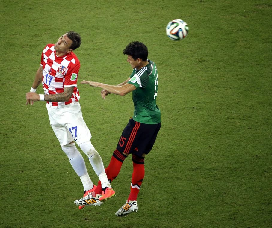 Croatia's Mario Mandzukic and Mexico's Hector Moreno challenge for the ball during the group A World Cup soccer match between Croatia and Mexico at the Arena Pernambuco in Recife, Brazil, Monday, June 23, 2014.