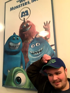 "image: Leo in front of a ""We're Monsters, Inc."" poster with four monsters posing jovially, while waiting in line for the ride"