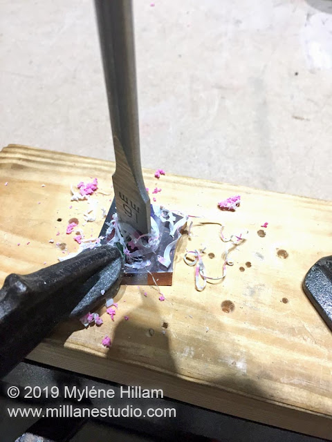 Using a spade bit to drill a hole in the resin slice to turn it into a ring