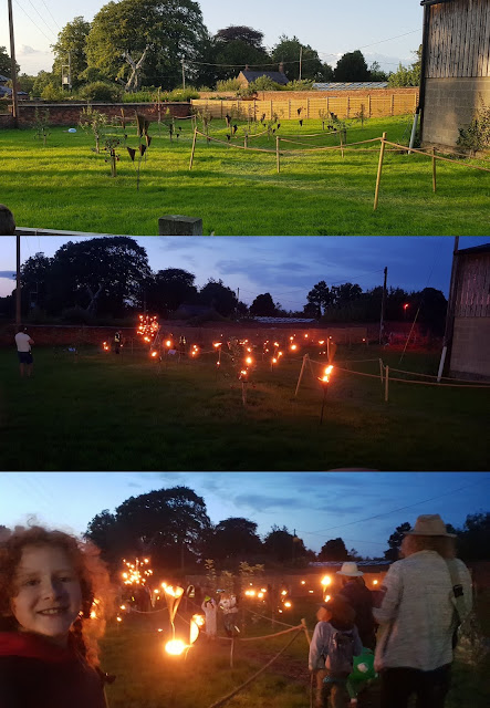 Just So Festival Fire Garden pathway with fire torches in the day and at night lit up