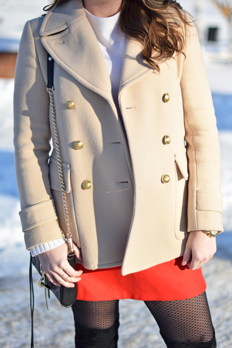 Button details on tan peacoat with black and gold bag.
