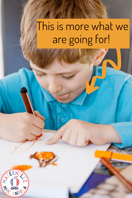 """This is a photograph of a young boy drawing with the text, """"This is more what we are going for"""" on it."""