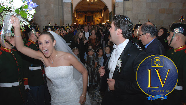 Novia feliz levanta el ramo a la salida de la misa recién casada