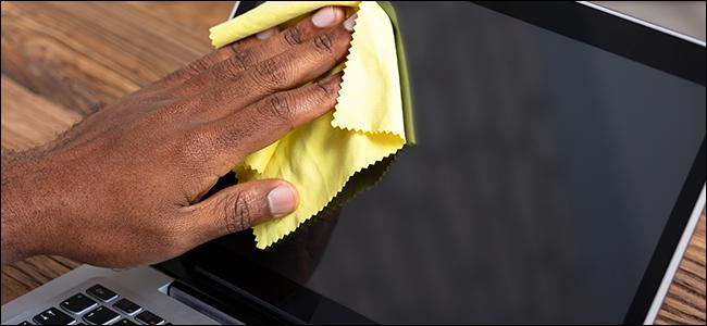 يد رجل تنظف شاشة كمبيوتر محمول بقطعة قماش من الألياف الدقيقة.