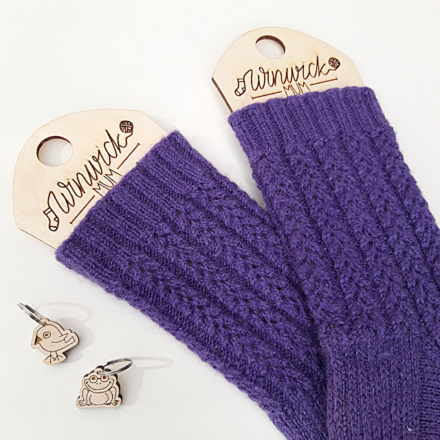 A pair of purple socks on sock blockers.  The blockers have Winwick Mum etched onto them.  There are 2 wooden stitch markers to the left - a frogs and a duck