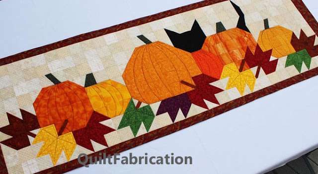 black cat hiding behind six pumpkins for a table runner pattern by QuiltFabrication