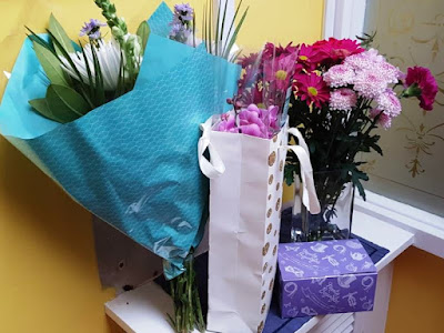 Two bunches of flowers, an orchid and a box of posh chocolates