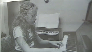 Ann Gotlib | a black and white photo of a girl playing a piano with her hair pulled into a ponytail | True Crime | mommalovestruecrime.com