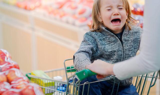 Criança no carrinho de compra fazendo birra