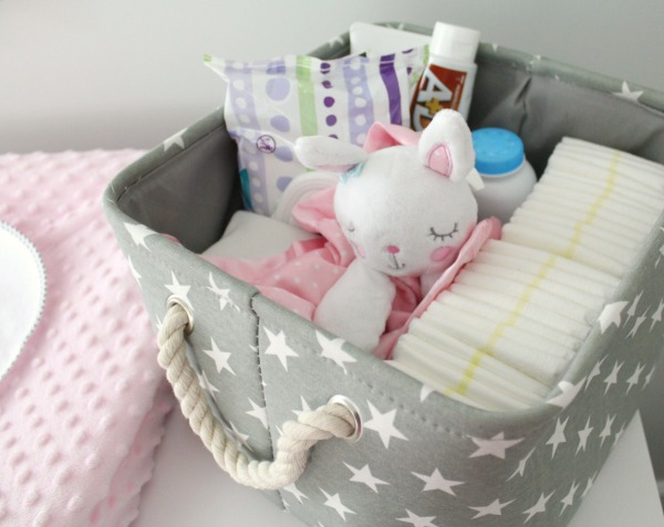 Gray white and light pink nursery for a baby girl- pink minky changing pad cover and gray canvas and rope basket with stars as a diaper caddy